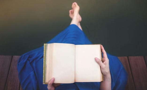 Junge frau, die durch flussufer sich entspannt. auf deck sitzen und leeres buch lesen Premium Fotos