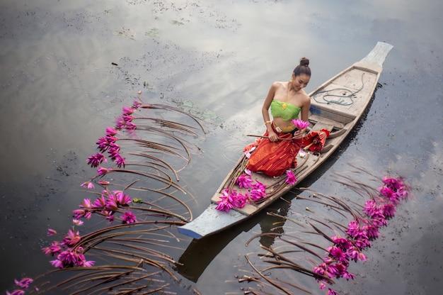 Junge frau, die durch rosa lotus on boat in lake liegt Premium Fotos