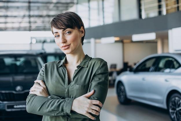 Junge frau, die ein auto in einem autohaus wählt Kostenlose Fotos