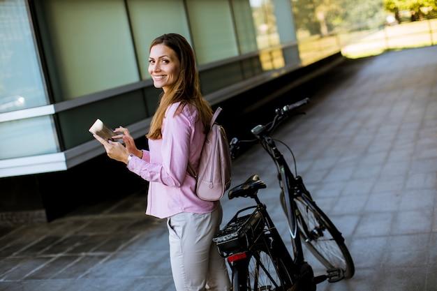Junge frau, die ein elektrisches fahrrad bereitsteht und digitale tablette in der städtischen umwelt verwendet Premium Fotos
