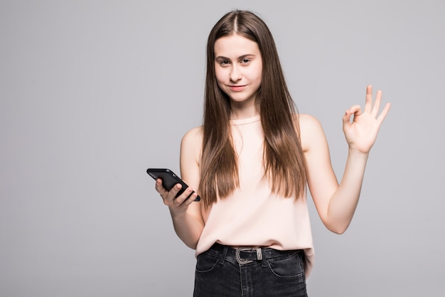 Junge frau, die ein gespräch spricht, das auf smartphone über isolierter wand spricht, die ok zeichen mit den fingern tut Kostenlose Fotos