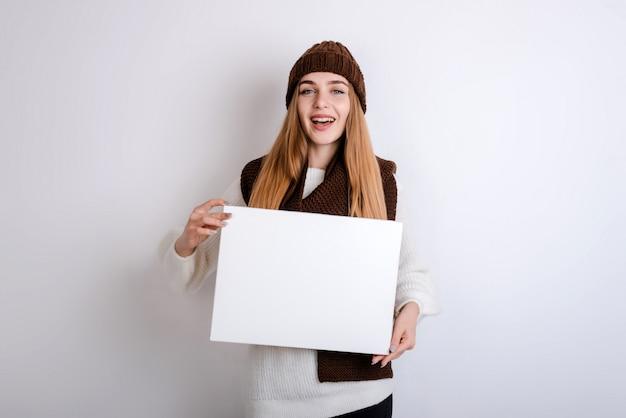 Junge frau, die ein leeres zeichen in der front oh ihr gesicht hält Premium Fotos