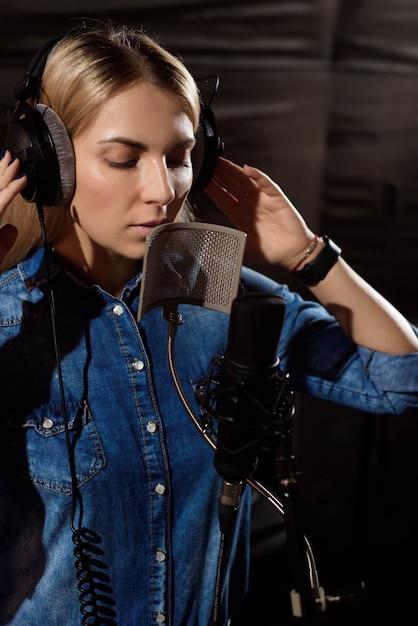 Junge frau, die ein lied im studio notiert. Premium Fotos
