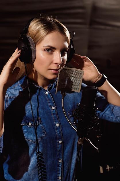 Junge frau, die ein lied im studio notiert Premium Fotos