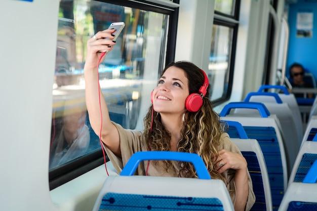 Junge frau, die ein selfie auf zug mit ihrem telefon nimmt. Premium Fotos