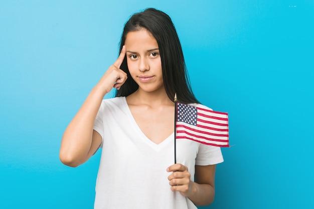 Junge frau, die eine flagge der vereinigten staaten hält, die seine schläfe mit dem finger zeigt, denkend, konzentrierte sich auf eine aufgabe Premium Fotos