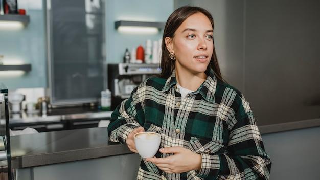 Junge frau, die eine kaffeepause genießt Kostenlose Fotos