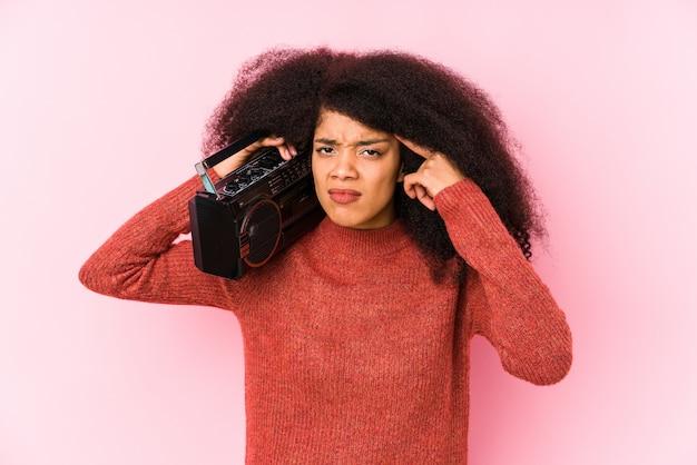 Junge frau, die eine kassette zeigt eine enttäuschungsgeste mit dem zeigefinger hält. Premium Fotos
