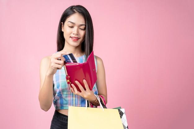 Junge frau, die eine kreditkarte von ihrem geldbeutel mit lächeln auswählt und einkaufstaschen trägt, Premium Fotos