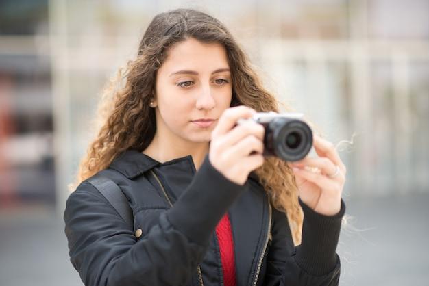 Junge frau, die eine mirrorless kamera verwendet Premium Fotos