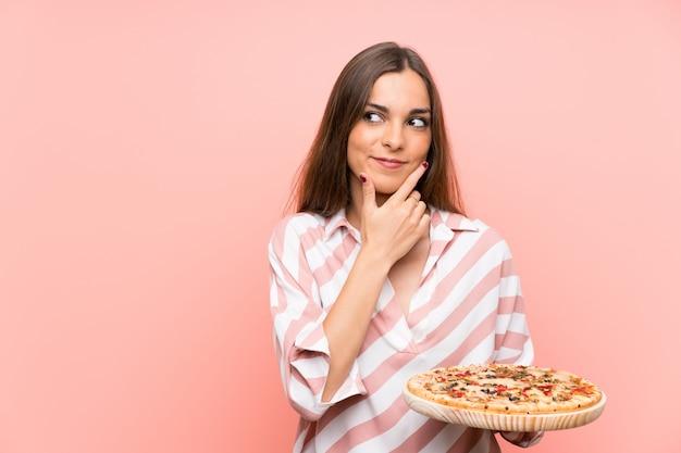 Junge frau, die eine pizza denkt eine idee hält Premium Fotos