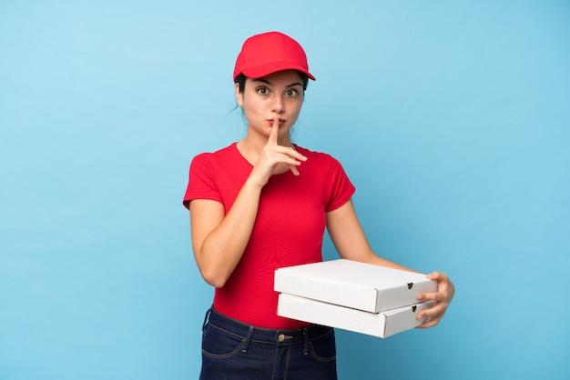 Junge frau, die eine pizza über der lokalisierten rosa wand tut ruhegeste hält Premium Fotos