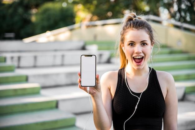 Junge frau, die einen smartphone hält Kostenlose Fotos