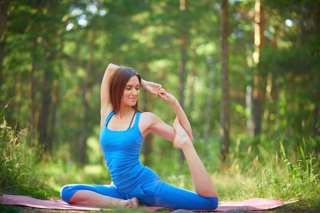 Junge frau, die einige gymnastische bewegungen zu üben Kostenlose Fotos