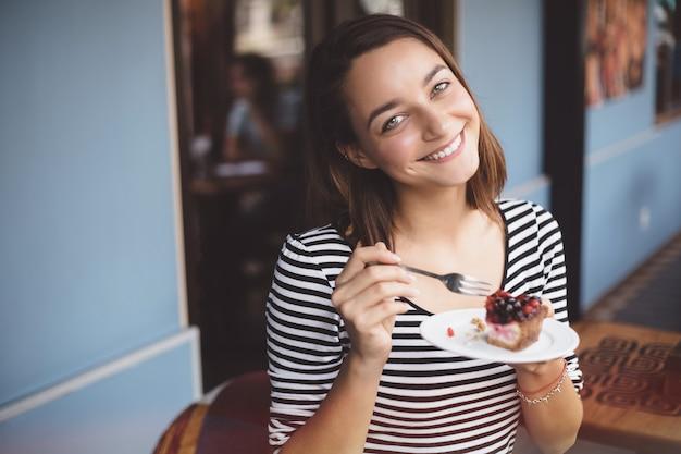 Junge frau, die erdbeerkäsekuchen isst Kostenlose Fotos