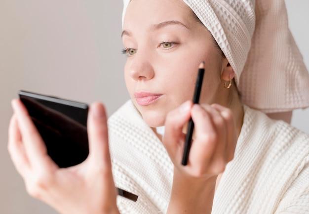 Junge frau, die eyeliner anwendet Kostenlose Fotos