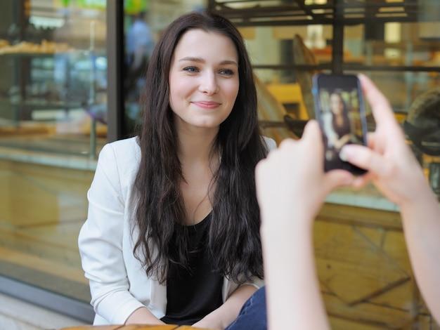 Junge frau, die foto ihres freundes macht Premium Fotos