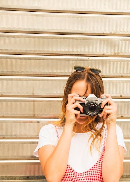 Junge frau, die foto mit kamera macht Kostenlose Fotos