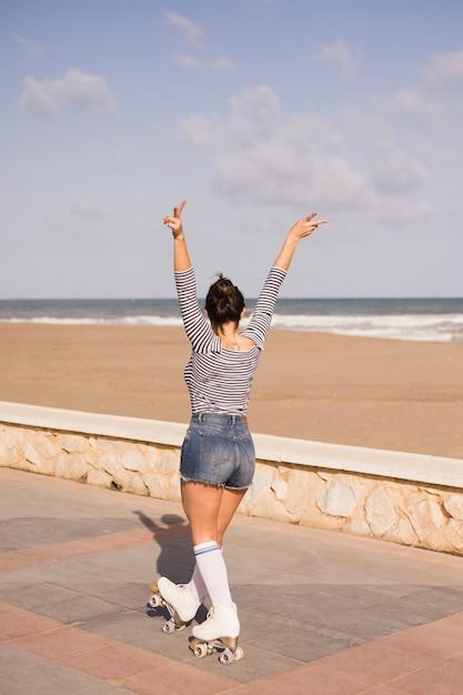 Junge frau, die friedenszeichen gestikulieren lässt, auf den seitenweg nahe dem strand zu gehen Kostenlose Fotos