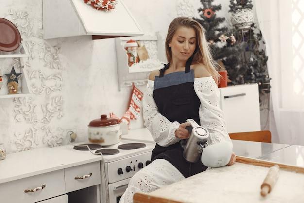Junge frau, die geformte kekse für weihnachten macht. wohnzimmer mit weihnachtsdekorationen im hintergrund verziert. frau in einer schürze. Kostenlose Fotos