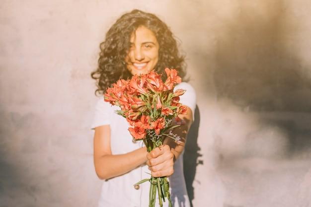 Junge frau, die gegen die wand hält roten blumenblumenstrauß der alstroemeria in den händen steht Kostenlose Fotos