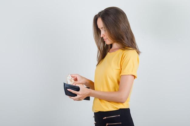 Junge frau, die geld aus der brieftasche im gelben t-shirt nimmt Kostenlose Fotos