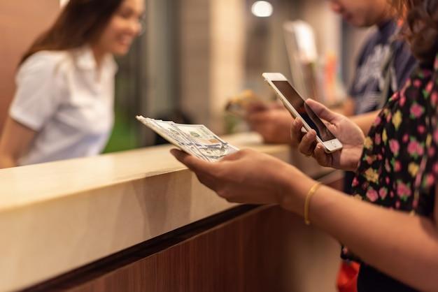 Junge frau, die geld hält und mobilen smartphone mit online-buchungsflug oder -hotel des knopfes verwendet. Premium Fotos