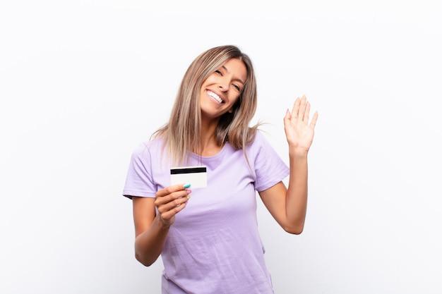 Junge frau, die glücklich und fröhlich lächelt, hand winkt, sie begrüßt und begrüßt oder sich mit einer kreditkarte verabschiedet Premium Fotos