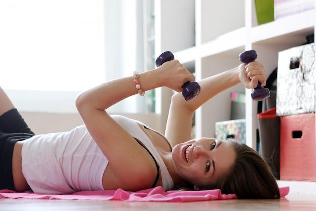 Junge frau, die gymnastikübungen tut Kostenlose Fotos