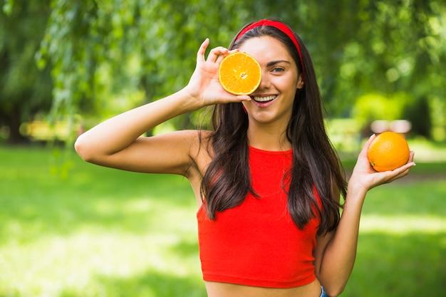 Junge frau, die halbierte orange vor ihrem auge hält Kostenlose Fotos