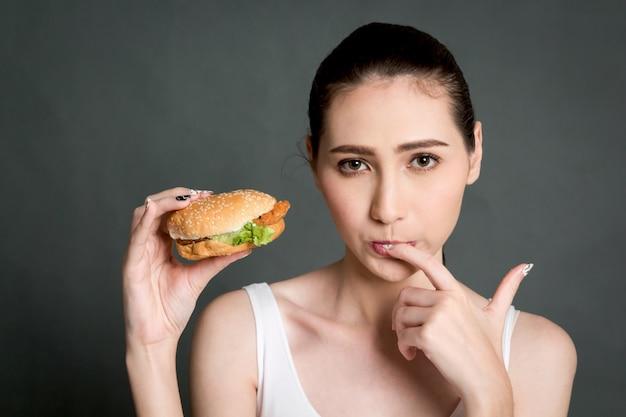 Junge frau, die hamburger auf grauem hintergrund isst. junk food und fast food konzept Premium Fotos