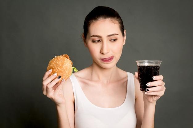 Junge frau, die hamburger und cola auf grauem hintergrund isst Premium Fotos