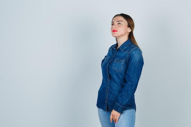 Junge frau, die hand auf hüfte hält, während sie im jeanshemd und in den jeans wegschaut und nachdenklich schaut Kostenlose Fotos
