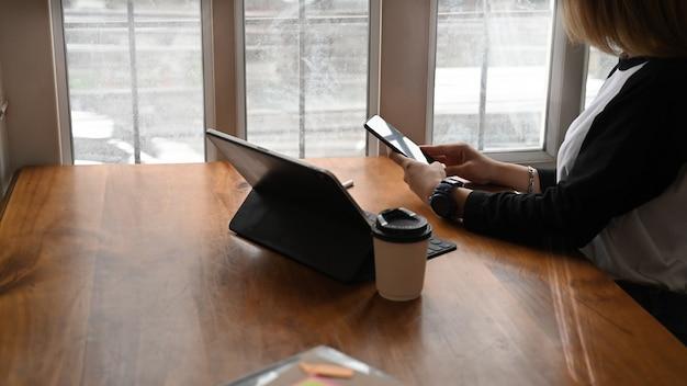 Junge frau, die handy auf büroarbeitsplatz verwendet. Premium Fotos