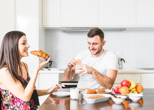 Junge frau, die hörnchen isst und ihr ehemann, der plätzchen in der küche isst Kostenlose Fotos