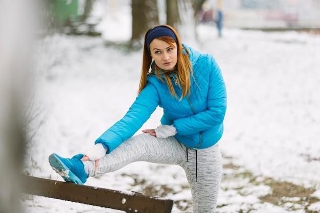 Junge frau, die ihr bein auf schneebedeckter landschaft in der wintersaison ausdehnt Kostenlose Fotos
