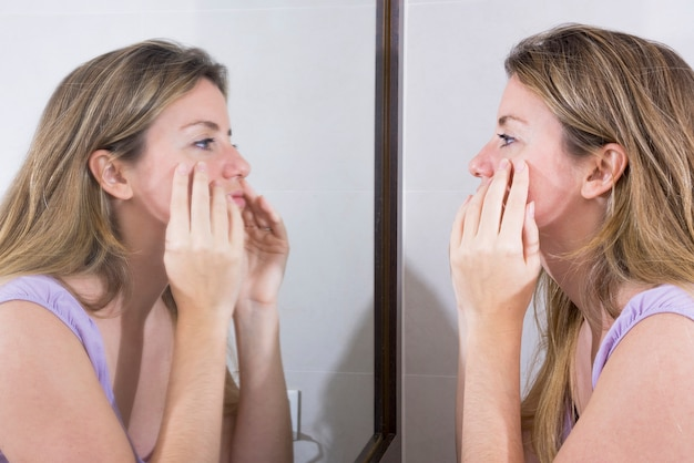 Junge frau, die ihr gesicht im spiegel überprüft Kostenlose Fotos