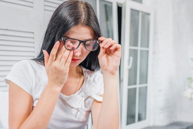 Junge frau, die ihre augen unter den brillen berührt Kostenlose Fotos