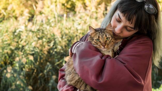 Junge frau, die ihre katze der getigerten katze im garten umarmt Premium Fotos