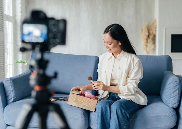 Junge frau, die ihre make-up-vorräte beim vloggen zeigt Premium Fotos