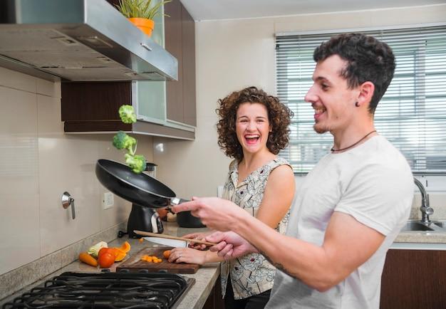 Junge frau, die ihren ehemann wirft brokkoli in der bratpfanne betrachtet Kostenlose Fotos
