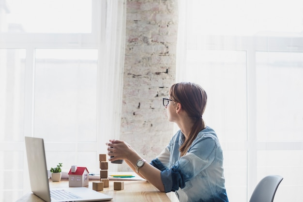 Junge frau, die im büro hält kaffeetasse in der hand sitzt Kostenlose Fotos