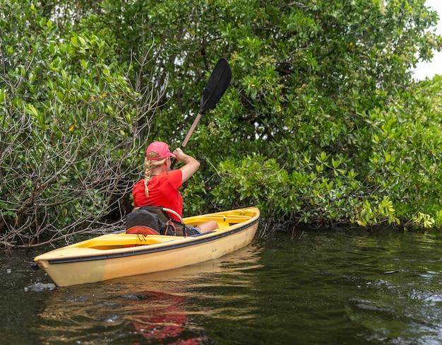 Junge frau, die im everglades-nationalpark kayak fährt Premium Fotos