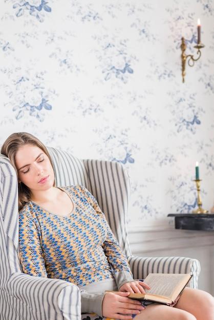 Junge Frau, die im Lehnsessel mit Buch in ihren Händen schläft Kostenlose Fotos