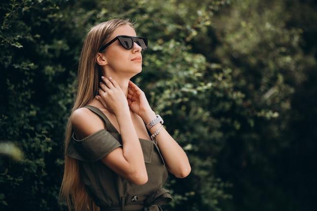 Junge frau, die im park auf dem grünen buschhintergrund steht Kostenlose Fotos