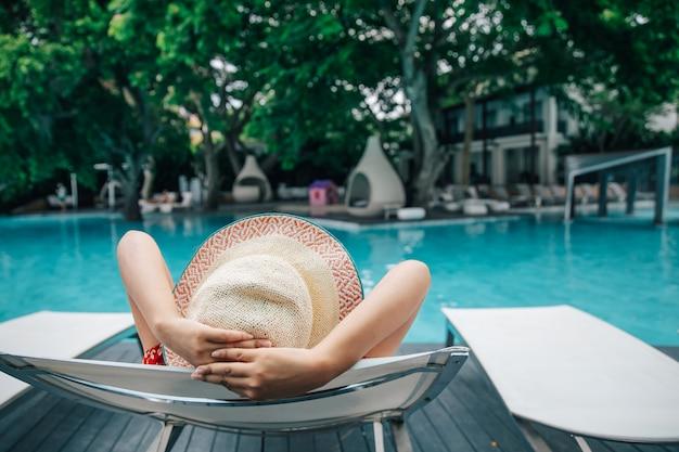 Junge frau, die im swimmingpool am kurort sich entspannt. Premium Fotos