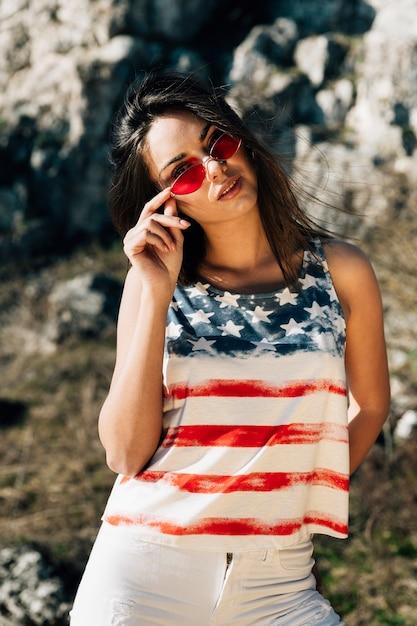 Junge frau, die im t-shirt der amerikanischen flagge aufwirft Kostenlose Fotos