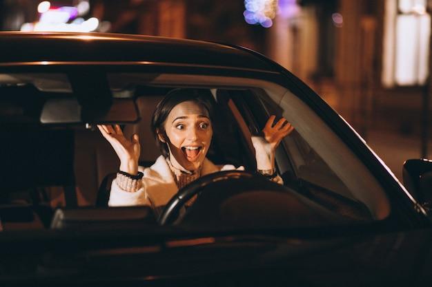 Junge frau, die in auto nachts fährt Kostenlose Fotos