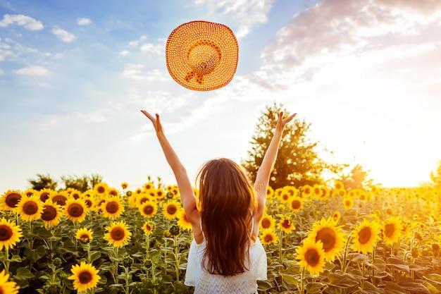 Junge frau, die in blühenden werfenden hut des sonnenblumenfeldes geht und spaß hat. sommerurlaub Premium Fotos