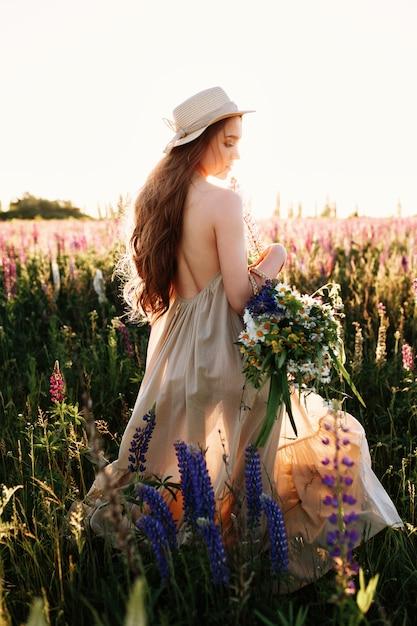 Junge frau, die in blumenfeld und in tragendem hut und kleid des hohen grases geht. Kostenlose Fotos